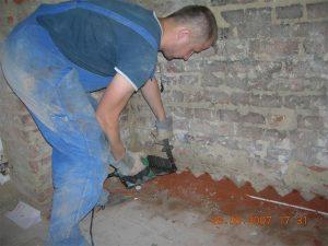 Budowlaniec wiercący otwór w ścianie